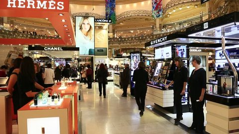PARIS, FRANCE - OCTOBER : inside part of the famous Galeries Lafayette store with it's brand stands stalls such as Chanel and Hermes and people shopping and sellers working on October 17th, 2013.