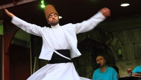 ISTANBUL - JUL 25, 2012: Sufi whirling dervish (Semazen) dances at Sultanahmet during holy month of Ramadan.Semazen conveys God's spiritual gift to those are witnessing ritual. He spins with the music