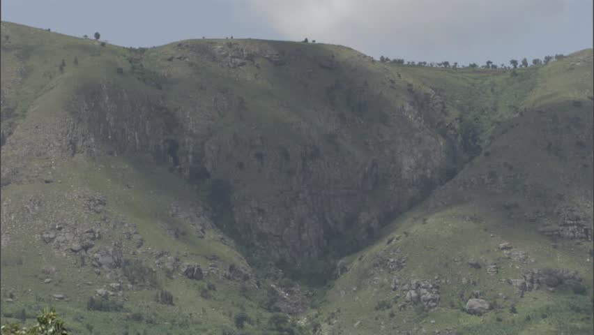 Rocks and shrubs scattered on the side of a Ugandan mountain. | Shutterstock HD Video #7741285