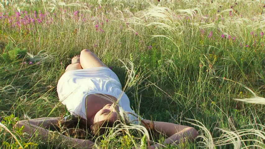 Girl resting on the nature. Beautiful girl lying on the field. Then the rolls from the back to back. Moving camera.