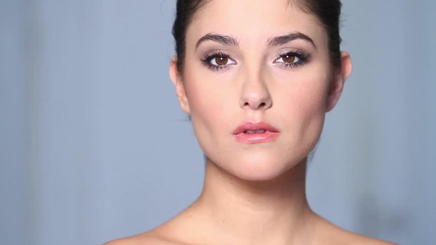 Beautiful young woman applaying cosmetics