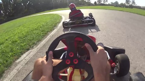 two drivers  drive go kart and overtaking on outdoor track, camera is attached to the helmet