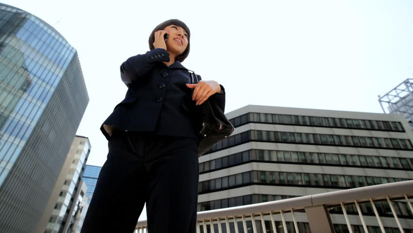 Ambitious ethnic Asian Japanese girl advertising business manager outdoors downtown buildings wireless hotspot smart phone connection   Shutterstock HD Video #7828705