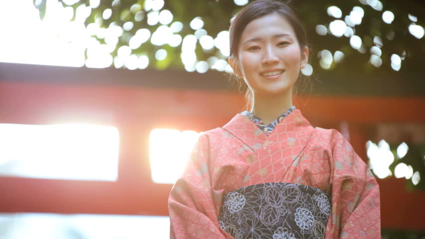 Asian Japanese woman red kimono costume Japan travel tourism temple vacation outdoor gardens location traditional bow