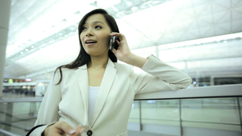 American Asian Chinese woman airport passenger travel business wireless smart phone information departures luggage executive traveller   Shutterstock HD Video #7853875
