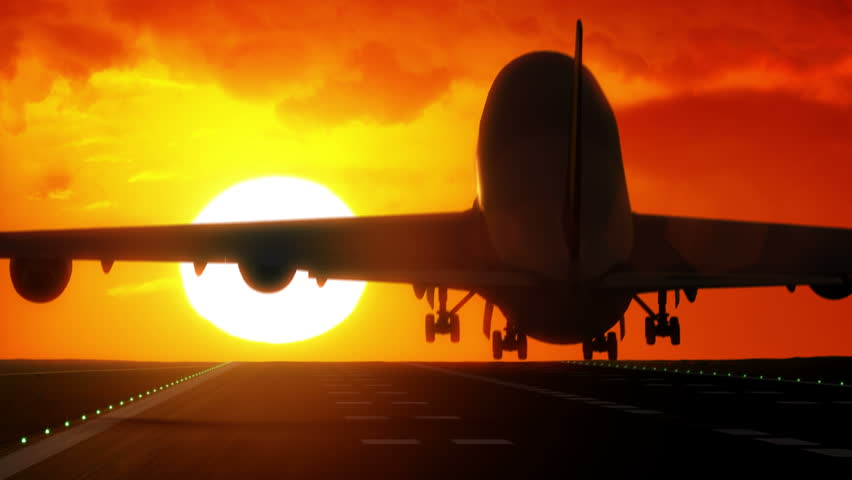Jet plane lands on airport runway as silhouette in front of large sunset / sunrise 4K UltraHD