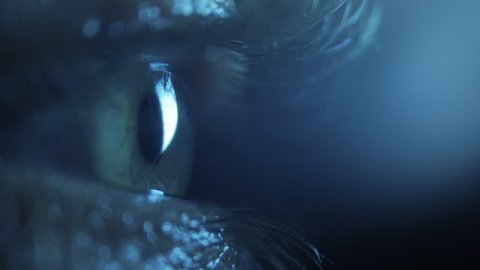 Pupil in the dark, close up. Eye blinks, looks around. Back light. Shallow depth of field