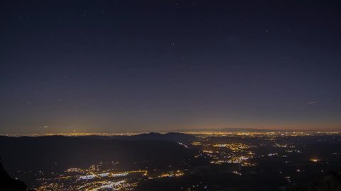 The moon moves across he glowing Seattle Metropolitan Area at night as seen from Mount Si.
