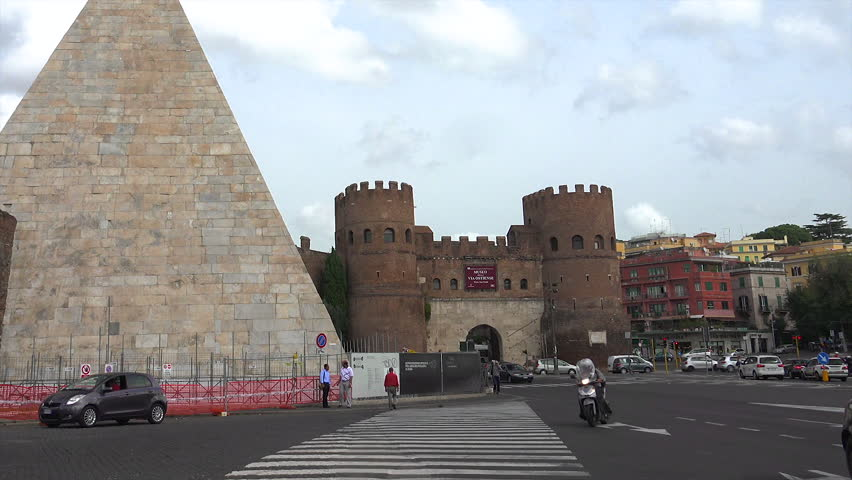 ROME - OCT. 2014: Cars pass through Porta San Paolo, zoom in to one almost colliding w motorcycle, past Pyramid of Cestius, or Piramide, built circa 18 BCE –12 BCE.  Museo della Via Ostiense in castle