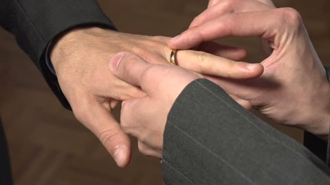 A close-up of the hands of two Caucasian gay men as they put wedding rings on each other.