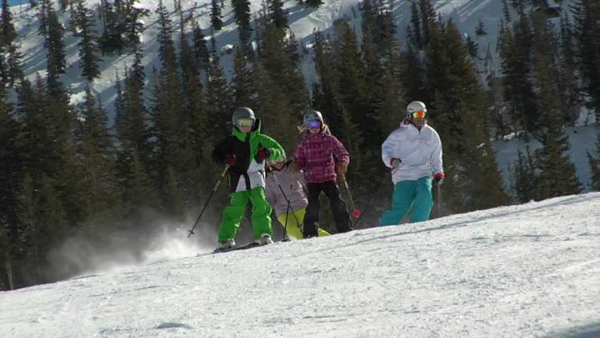 Healthy family snow skis on sunny, winter slope, Utah.