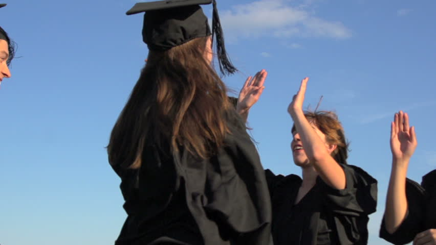 University students in academic gowns and mortarboards hi five in celebration at their graduation. Camera dollies back and forth against blue sky in slow motion.