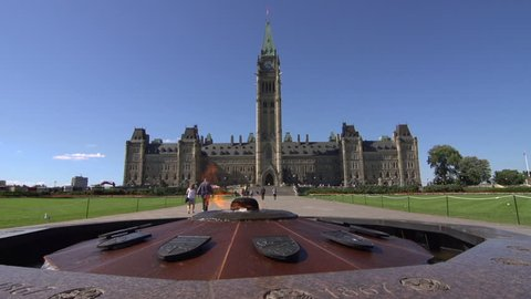 A pan left across the Centennial Flame, in front of Parliament, Ottawa, Canada as tourists walk towards the building.