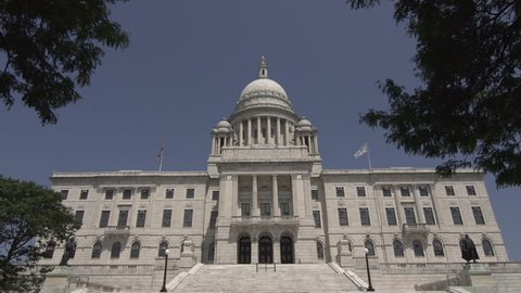 A tilt down to reveal a frontal shot of the exterior and steps of the Rhode Island State House in Providence, Rhode Island, USA