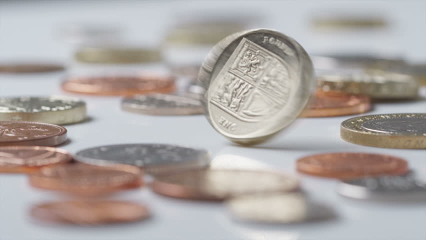 UK Currency one pound coin spinning amongst other UK currency coins in slow motion at 120fps, shot on RED EPIC