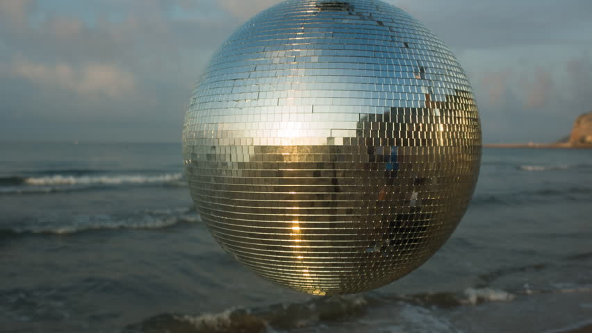 large spinning discoball on the beach with the sea in the background. very balearic clip useful for clubs, music and fashion events