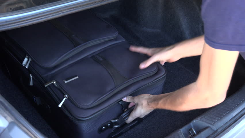Man packs luggage into car trunk for family car trip. 4K UHD 3840x2160 | Shutterstock HD Video #8012032