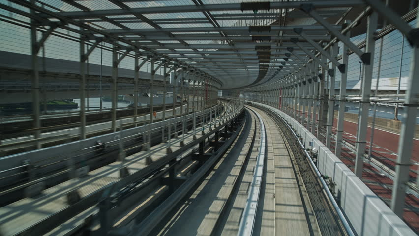 POV shot on the tokyo monorail passing through the city's skyscapers and futuristic style buildings