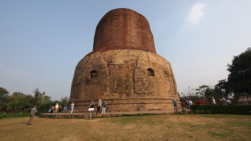 SARNATH, INDIA - FEBRUARY 19: Visitors at the Dhamekh Stupa, site where Gautama Buddha first taught the Dharma after attaining enlightenment, in Sarnath, Uttar Pradesh, India.