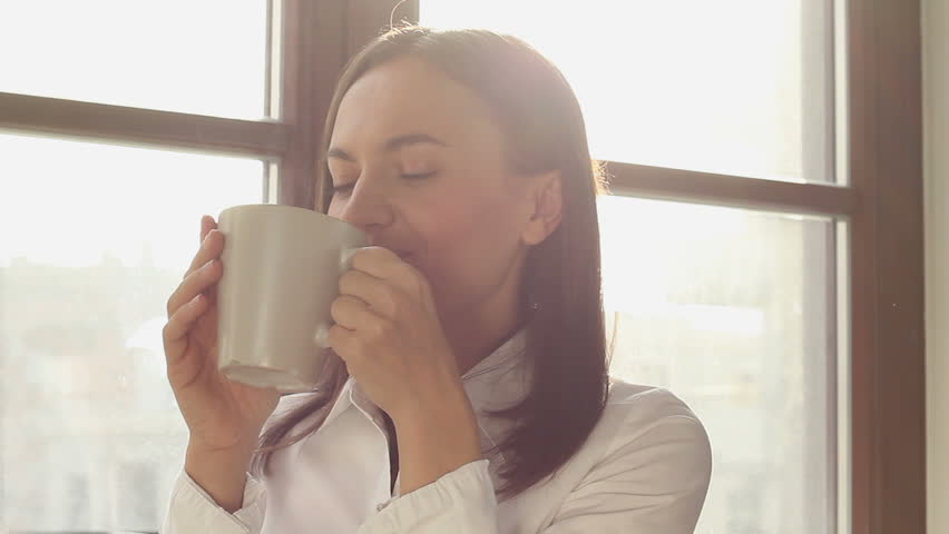 Beautiful young woman dreaming with cup of hot coffee over window