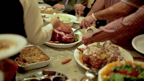 Thanksgiving Table with Turkey and Side Dishes and Man Carving, Slicing, and Serving Ham