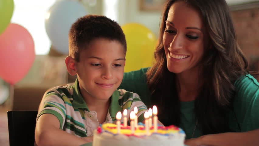 Mother and son blowing out the candles on a birthday cake together