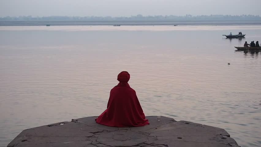 Varanasi, India - February 18: Sadhu (Indian holy man) sitting in meditation by the sacred Ganges river in Varanasi, Uttar Pradesh, India.