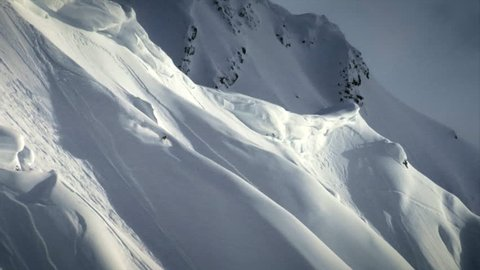A freestyle skier charges down a beautiful snow covered mountain in slow motion