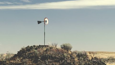 A Small Windmill Sits On Rock Outcrop As Strong Wind Blows In Eastern Washington