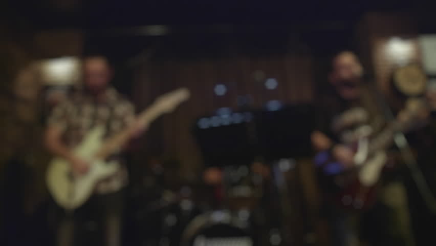 Guitar player  bassist and drummer performing instrumental live solo at a night music bar.Wide establishing shot out of focus.  | Shutterstock HD Video #8268244