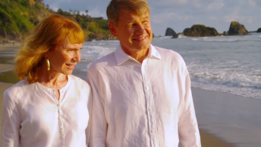 Older couple hold hands and walk on the beach together.