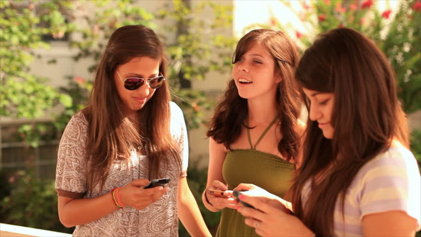 Teenage girls standing outside on a bright sunny day using their phones to send text messages to their friends.