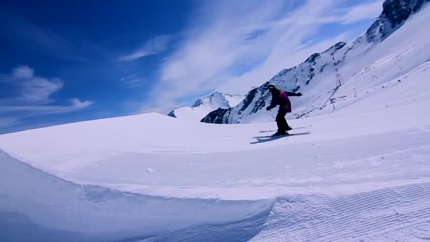 A skier jumps from a ramp before landing successfully on the slope | Shutterstock HD Video #8300125
