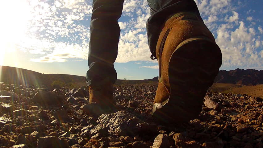 Low and wide angle shot of a man as he walks away from camera in a barren rocky desert. A hiker enjoys exploring a rough scenic landscape strewn about with small stones. | Shutterstock HD Video #8335927