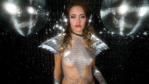 sexy disco party woman dressed in a unique silver costume with metal wings. Perfect for stylish club, disco and fashion events