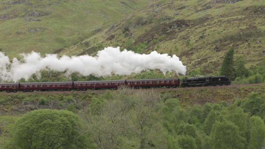 GLENFINNAN, SCOTLAND - MAY 2014: Stunning shot of the Jacobite Steam Train going over the Glenfinnan viaduct in the Scottish highlands