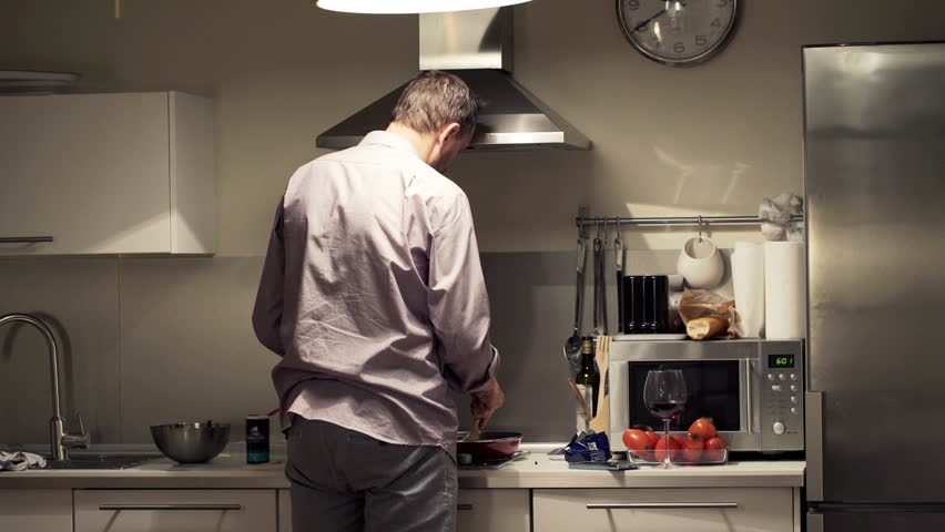 Man cooking, checking recipe on smartphone and adding seasoning in kitchen at home