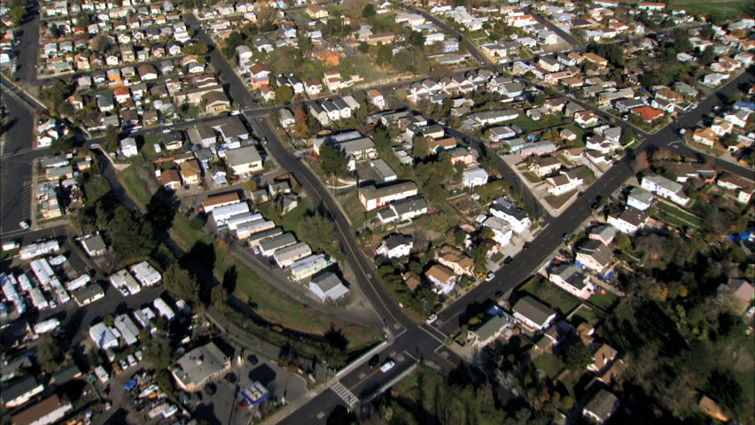 Aerial view of rooftops of housing in city suburbs by industrial oil refinery