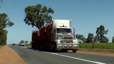 BOYUP BROOK, AUSTRALIA - OCTOBER 2014: A road train carrying timber logs driving down a highway in rural Australia.