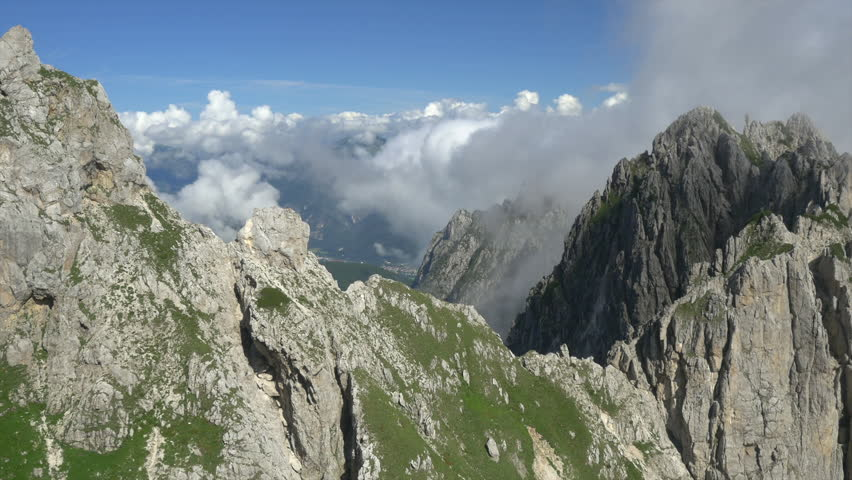 AERIAL: Over the mountain cliff towards the mountains