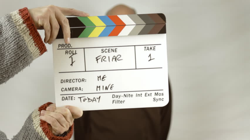 Using a movie slate to start the shooting of a man dressed as a friar (Franciscan dress clothes) against a white background. The actor is slightly defocused, the clapperboard is in focus.