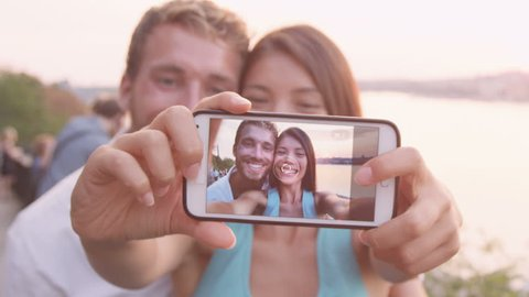 Smart phone selfie - couple taking self portrait using smartphone camera. Dating couple in love having fun taking candid fresh picture photo laughing smiling. Caucasian man, Asian woman at sunset.