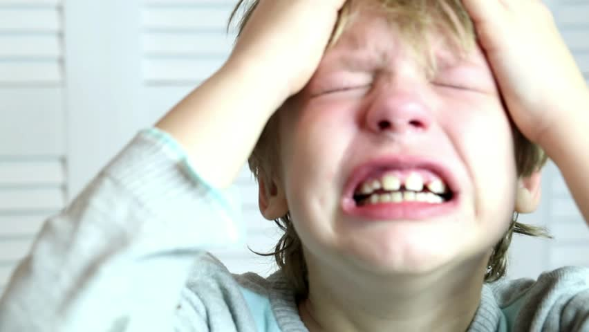 Portrait of caucasian 8 years old boy hardly crying and screaming in panic. Parenting, violence in family, feelings and emotions concept. Close up of face with tears of desperate and disappointed kid.