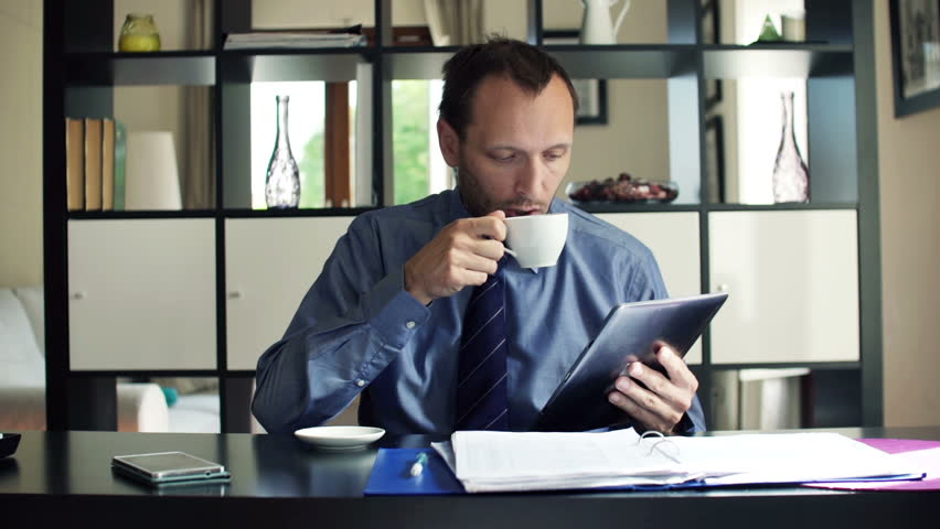 Businessman reading article on tablet computer and drinking coffee at home