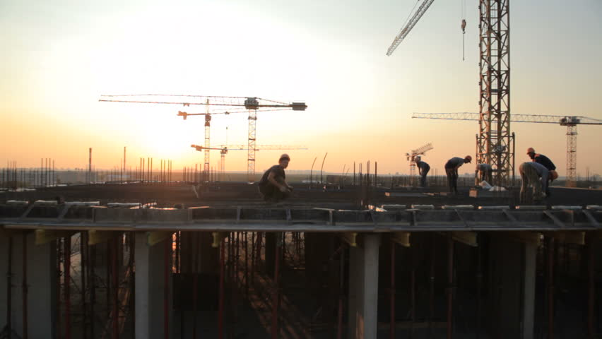 MOSCOW,RUSSIA 2014:Industry construction and development. Workers building a new house.Aerial shot.The camera moves from the top down. Workers are working in the backlight of the sun at sunset