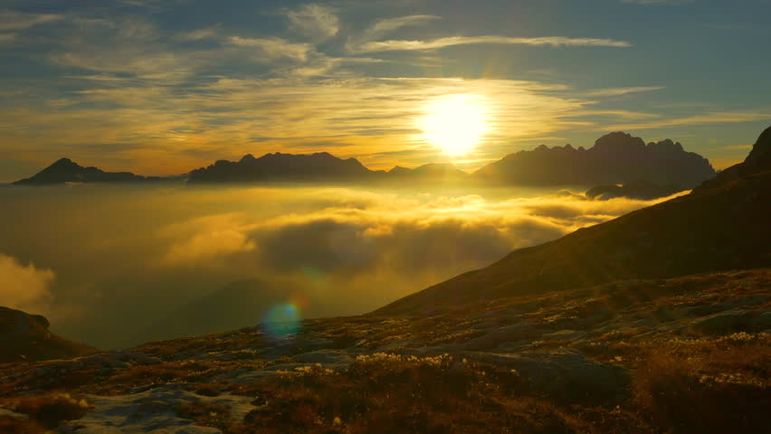AERIAL: Sunset above the clouds on top of the mountain #8478505