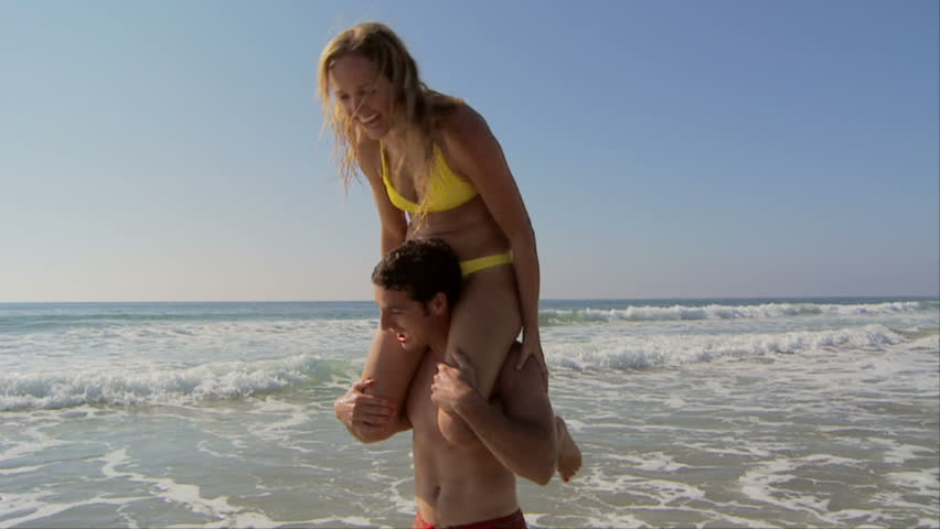 Young couple at beach giving piggy back rides