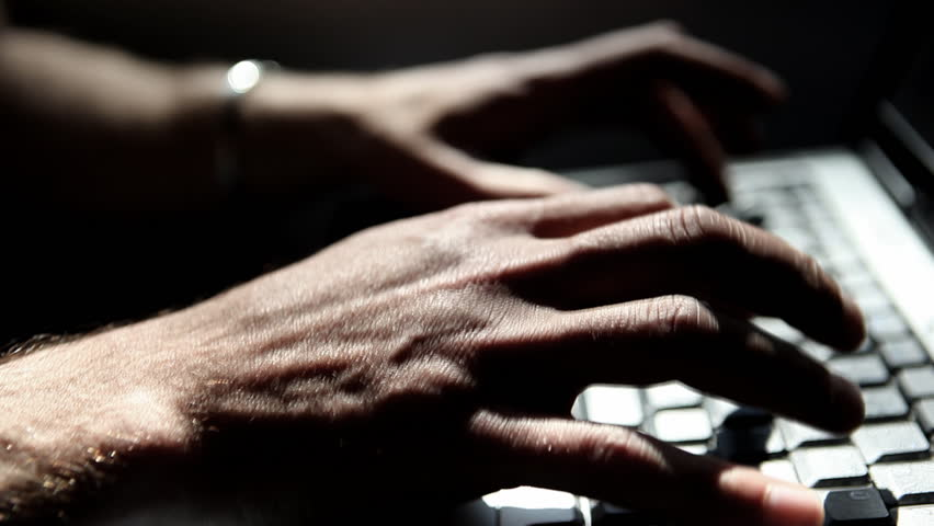 Close-up of hands working on laptop during a train ride, nice light effects by