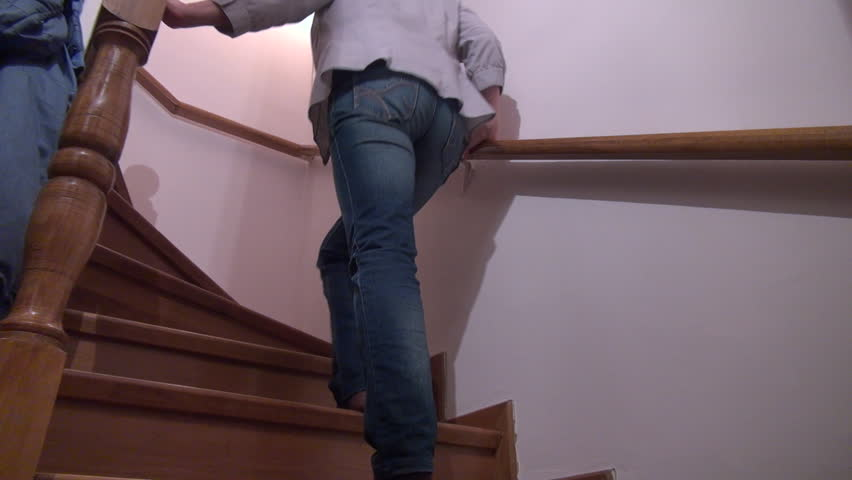 Woman having low back pain while walking up the stairs