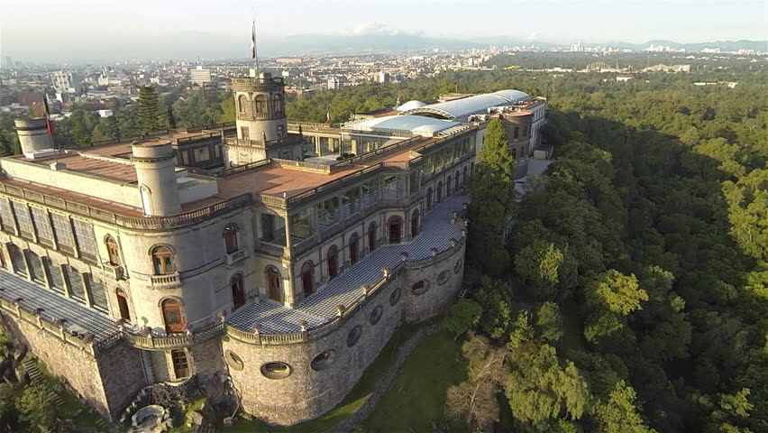 Aerial top view of the Chapultepec Castle at the top of the hill with the forest surrounding it and a view of part of Mexico City behind in a very sunny morning